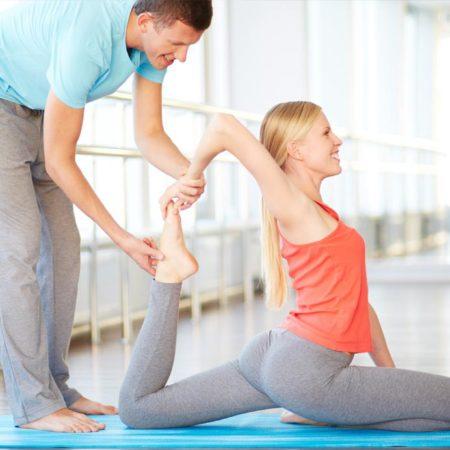 istruttore che aiuta una ragazza a fare un'esercizio di strathcing
