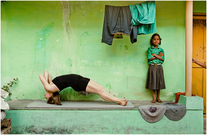 donna occidentale che fa yoga in India con bimba indiana che sorride