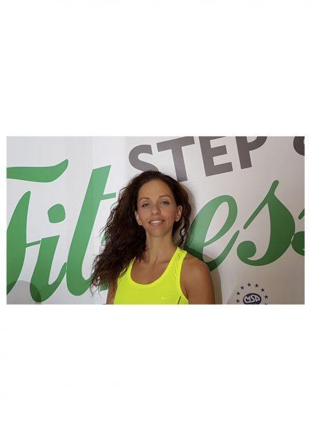 Deborah Nieco istruttrice della Step&Fitness Studios davanti al cartellone pubblicitario della palestra