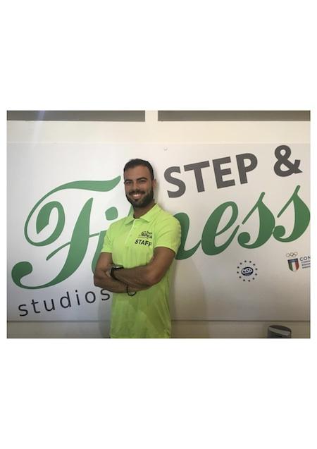 Francesco Fadda istruttore della Step&Fitness Studios davanti al cartellone pubblicitario della palestra
